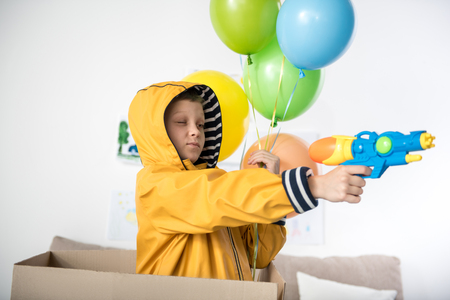 Cheerful kid playing with water gun in living room, he is holding balloons in hand