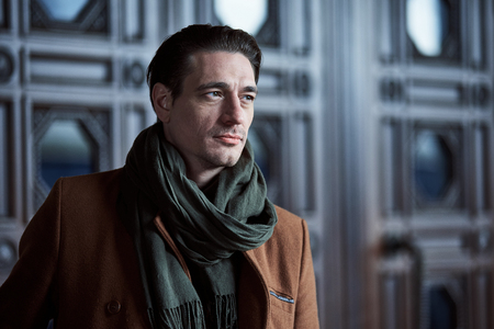 Porträt des ruhigen modernen Mannes , der nahe altem Gebäude draußen sich lehnt . Reisekonzept Standard-Bild - 93598813