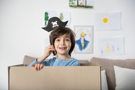 Portrait of jolly little lad standing inside of carton and holding paper pirate hat above his head. Copy space in right side Foto de archivo
