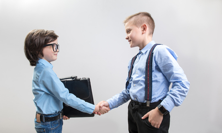 Congratulations. Side view profile of two boys colleagues making a deal. They are looking at each other with satisfaction and shaking hands. Isolated on background