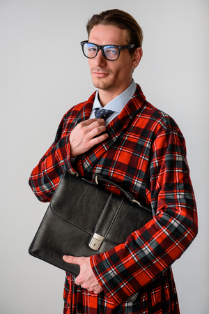 Waist up portrait of successful guy holding briefcase and adjusting tie. He is looking at camera. Isolated on grey background Stok Fotoğraf