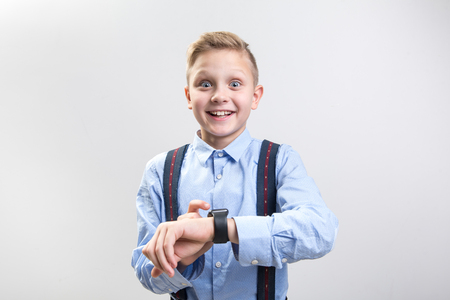 Waist up portrait of excited trendy schoolboy testing his new smartwatch. Isolated on background