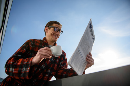 Oh really. Low angle of surprised guy finding out news. He is standing on terrace with coffee and journal in his hand