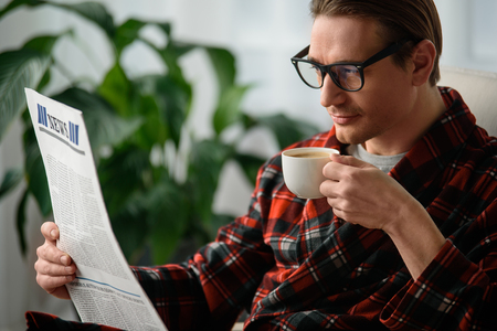 Tranquil guy holding the journal and cup in the hand. He is reading news with intent look and drinking coffee in bedroom Stock Photo