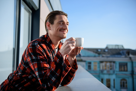 Cheerful adult man reaxing on terrace and wearing bathrobe. He is holding a cup of coffee in his hands and looking with smile