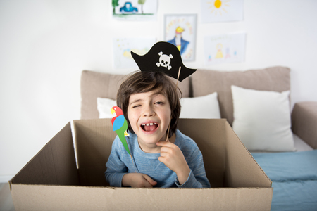 Ahoy. Portrait of funny kid with paper parrot and pirate hat, boy is hiding inside of carton box and winking at camera cheerfully Stock Photo