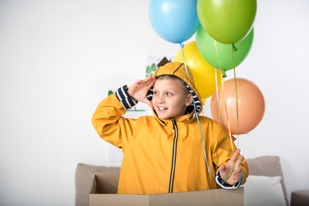 Waist up of cheerful kid in yellow raincoat standing in carton box with balloons in his hand and looking aside Stock Photo