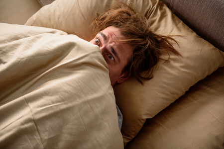 Feeling frightened. Scared adult male lying in bed and covering his head with a blanket in bedroom 스톡 콘텐츠