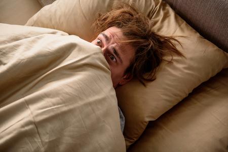 Angstig voelen Bang volwassen mannetje dat in bed ligt en zijn hoofd bedekt met een deken in de slaapkamer