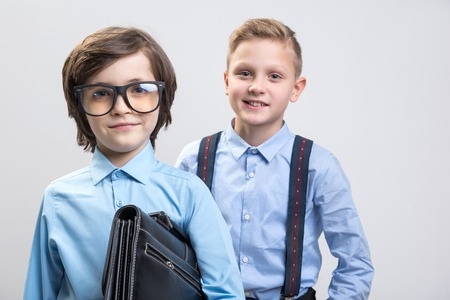 大きくなったらビジネスマンになることを夢見ている笑顔の小さな男の肖像画をウエストアップ。彼らはエレガントな服を着ている。バックグラウ