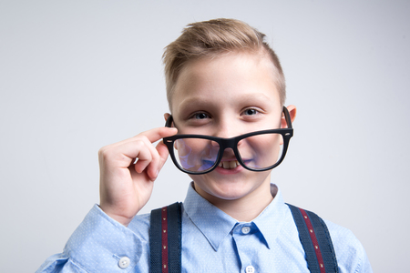 Portrait of intelligent child wearing glasses and looking with joy. Isolated on background Stock Photo