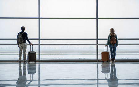 Unacquainted man and woman standing with bags in different parts of the airport hall