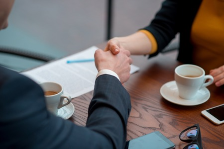 It is good job. Close up girl arm shaking hands with partner. They sitting at table. Profession concept