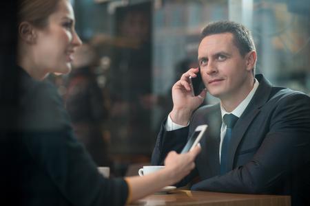 Glücklicher Mann, der telefonisch beim Trinken des Tasse Kaffees mit abgehender Dame im Restaurant spricht. Frohe Kollegen, die am Schreibtisch finden. Konzept zu brechen Standard-Bild