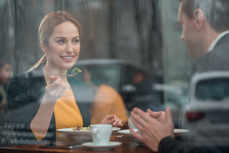 Portrait of cheerful lady eating appetizing meal while speaking with colleague. They sitting at table in cafe. Communication and leisure concept