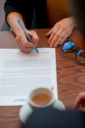 Close up woman arm inking deal with partner while situating at table. Career concept