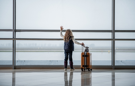 Small child flying to the destination. She is saying goodbye to the departing aircraft. Copy space in left side