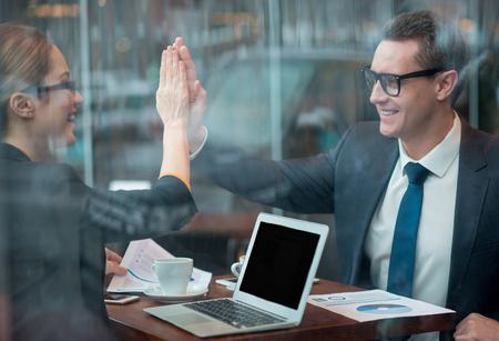 We zijn een goed team. Zijaanzicht vrolijke dame die high-five met gelukkige collega doet. Prestatie concept