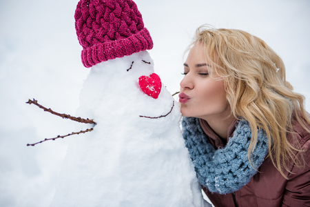 Pretty blond girl is kissing self-made snowman for fun. Her eyes are closed