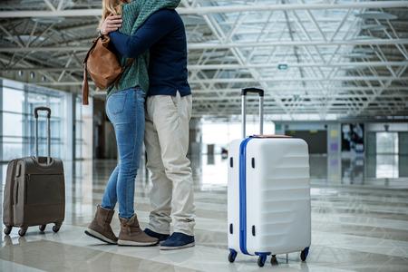 若い人たちは長い旅行の前にさよならを言う。彼らはお互いに抱き合っている。スーツケースに焦点を当てる 写真素材