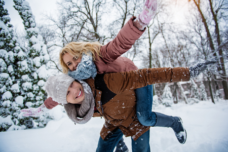 We are free. Joyful loving couple is having fun in winter park. Guy is keeping girl on back and laughing. They are stretching arms sideways Archivio Fotografico