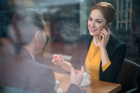 Portrait of beaming businesswoman talking by phone while situating at table with colleague. He turning back to camera. Communication and relax concept Фото со стока