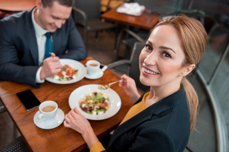 Portrait of outgoing lady eating appetizing salad while sitting at table with smiling partner. She looking at camera. Lunch concept Imagens
