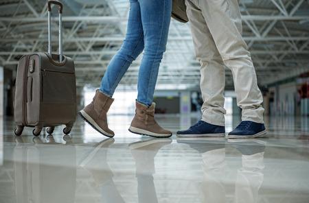 男性と女性の足が互いに近くに立っています。荷物は近くにあります。クローズアップ