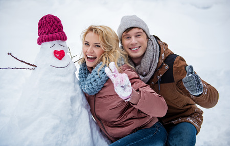 Portrait of happy loving couple is posing near self-made snowman and gesturing. They are looking at camera and smiling. Winter holidays concept
