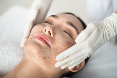 Close up of asian girl enjoying skin care treatment. Beautician hands pampering her face with scrub Banque d'images