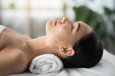 calme jeune femme est relaxant au salon de beauté . il est un mouchoir sur son visage . les yeux sont fermés avec plaisir