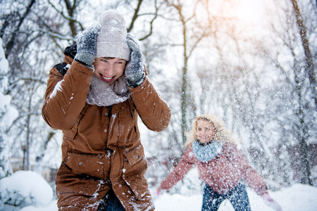 Focus on portrait of joyful young man hiding from flying snow and smiling. Young woman is throwing snowball on him on background