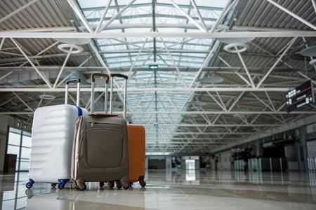 Three big suitcases standing close at the terminal hall. Copy space in right side