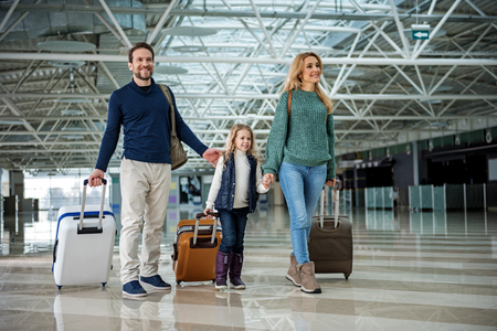 Full length of happy family walking through airport. Everyone carrying own suitcase