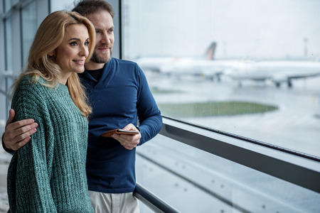 Hugging happy man and woman watching airplane going along the runway. Copy space in right side