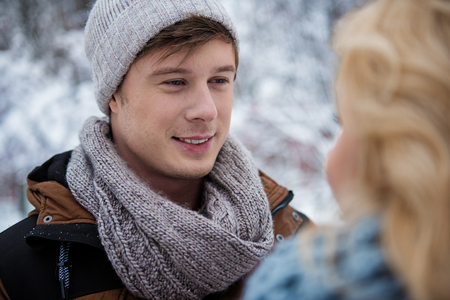 Portrait of happy young guy looking at girl with love and smiling. They are standing outdoor in winter