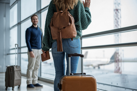 Man and woman splitting off in different directions in the terminal. Focus on lady waving to guy Stock Photo