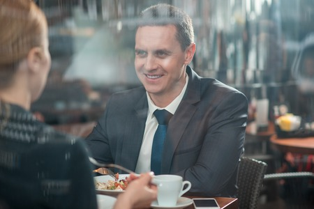 Portrait of outgoing male talking with woman while eating salad in cafeteria. Lunch concept