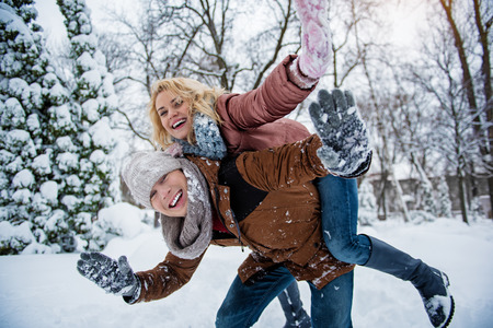 Cheerful young man and woman are playing in winter forest. They are stretching hands forward and laughing. Girl is sitting on male back for fun