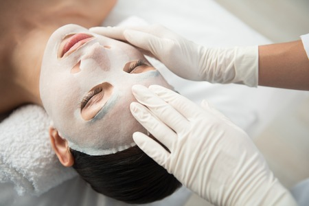 Top view close up of cosmetician hands putting textile mask on woman face Stock Photo