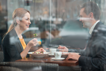Side view smiling female and outgoing businessman eating portion of salad while sitting at desk in cafe. Lunch concept