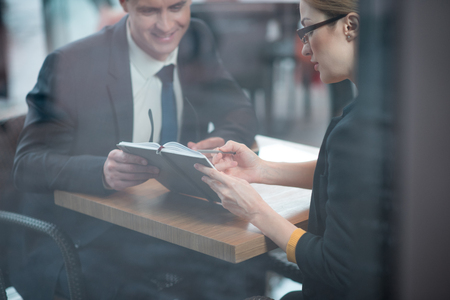 Smiling businessman and calm female watching at appointment book. They sitting at desk indoor. Career and discussion concept