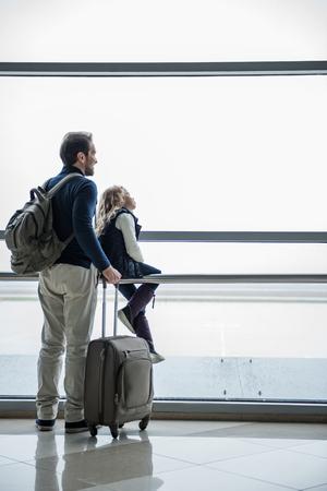 疲れ果てた父と娘は長い間空港に滞在した。彼らのフライトは欠航になった。右側にスペースをコピーする