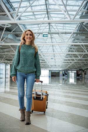 搭乗中に荷物を運ぶ笑顔の女性の全長の肖像画。右側にスペースをコピーする