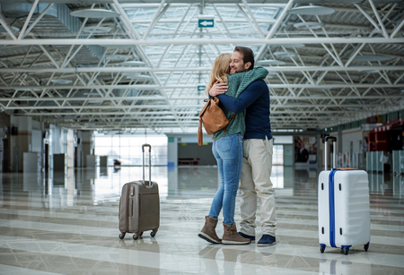 Two cheerful adults hugging each other before departure while standing in the terminal. Suitcases are apart of them Imagens