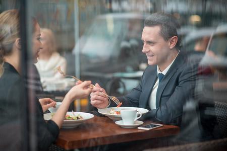 陽気な女性と語る笑顔の男のサイドビュー。カフェのデスクに座りながら食欲をそそる料理を味わう。ディナーコンセプト 写真素材