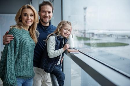 飛行機が到着するのを待っているうれしい親戚。彼らはカメラを見て微笑んでいる。右側にスペースをコピーする