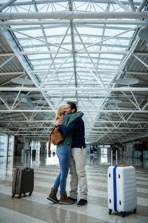 空港で楽しい男女の出会い。彼らはお互いを抱きしめている。手荷物は別に 写真素材