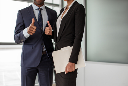 It is Ok. Confident successful business partners are standing together in light office and showing thumbs up. Close-up of hands of man and woman
