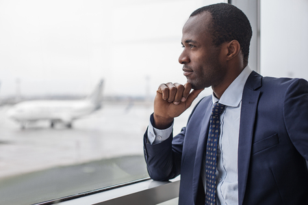 Lost in thoughts. Profile of pensive young stylish entrepreneur is standing at airport building. He is leaning elbow on window while touching his chin and enjoying view. Copy space in the left side